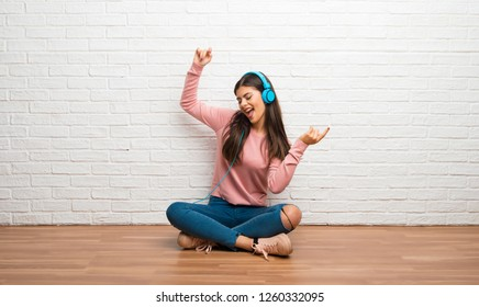 Teenager girl sitting on the floor in a room listening to music with headphones and dancing