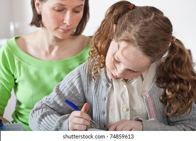 Teenager girl sitting together with her mother and showing her homework