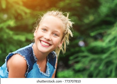 Teenager girl smiling with perfect smile and white teeth in the park .