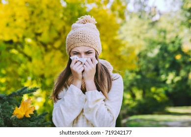 teenager girl sneezes in a handkerchief on the street in autumn