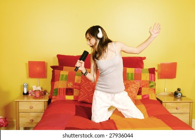 Teenager girl standing in a bed and singing with a hairbrush