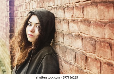 Teenager girl with streaming curly foxy hair in smock standing near the brick wall. Problems of depression, dependence and conflict. Psychology teenager.