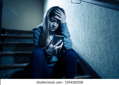 Teenager girl victim of online stalker suffering from cyberbullying abuse feeling lonely and hopeless sitting on stairs with dark light. Dangers of internet, online grooming and harassment concept.