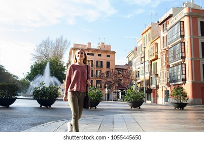 Teenager girl walking in destination city street with character buildings, sightseeing on holiday, sunny outdoors. Tourist young woman enjoying vacation, active travel recreation leisure lifestyle.