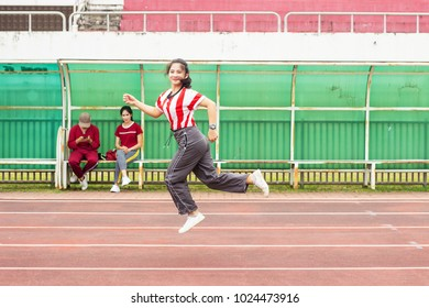 Teenager girl wear sport cloth run on racetrack, jumping and exercise for health. Healthcare and sport concept. Free space for your text.