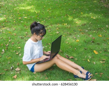 Teenager girl wearing a glasses with computer sitting on the green grass.
