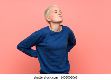 Teenager girl with white short hair over pink wall suffering from backache for having made an effort