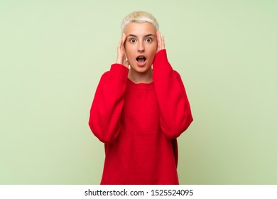 Teenager girl with white short hair over green wall with surprise expression