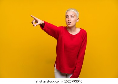 Teenager girl with white short hair over yellow wall pointing away