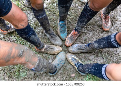 Teenager girls put their feet together to show their mud covered soccer shoes during their soccer game