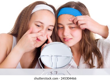 Teenager girls searching for blemishes on theirs skin