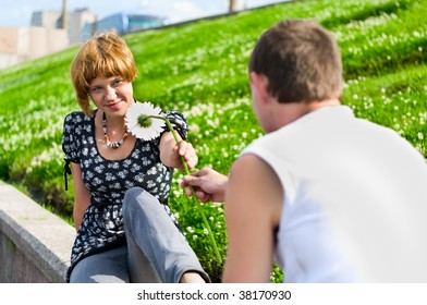 Teenager gives flower to girlfriend. Outdoor.