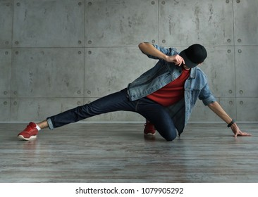 Teenager guy in denim jacket and baseball cap, jeans and red sweater dances of break dance. Dynamics of modern dance movement. Youth fashion. Man is unrecognizable