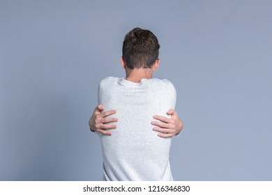 Teenager guy hugging himself over gray background