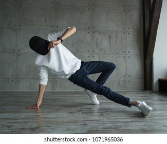 Teenager guy in a white sweater and a baseball cap, jeans and sneakers doing breakdancing in a dance studio. Dynamics of modern dance movement. Man is unrecognizable