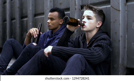 Teenager guys drinking beer sitting on road, bad company influence, experience