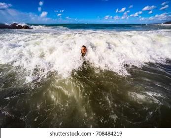 teenager having fun in the sea waves - summertime - Sicily mediterranean sea