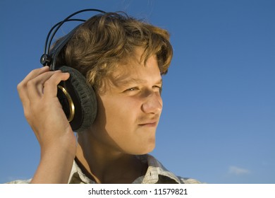 Teenager in headphones on blue sky background. Close-up.