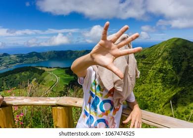 "teenager hidden face in the beautiful view of Lake Sete Cidades ""Lagoa das Sete Cidades"" in Sao Miguel, Azores, Portugal"