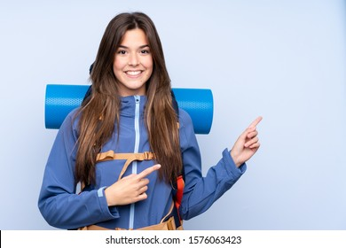 Teenager hiker girl over isolated background pointing finger to the side
