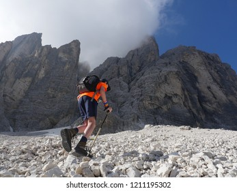 Teenager hiking up on gravel toward steep rockface, partly covered by a cloud