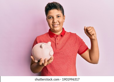 Teenager hispanic boy holding piggy bank screaming proud, celebrating victory and success very excited with raised arm