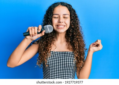 Teenager hispanic girl singing song using microphone screaming proud, celebrating victory and success very excited with raised arm