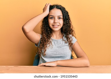 Teenager hispanic girl wearing casual clothes sitting on the table smiling confident touching hair with hand up gesture, posing attractive and fashionable  - Shutterstock ID 1951535443