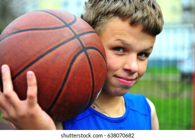 Teenager holding basketball in his hands on the court