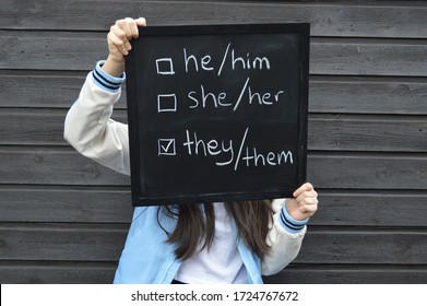 Teenager is holding a black board with text in white related to concept of gender identity and fluidity