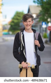 Teenager holding his longboard and smiling cheerfully to the camera. In the background a suburban setting.
