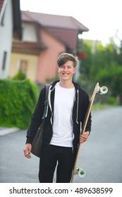 Teenager holding his longboard in a suburban setting.