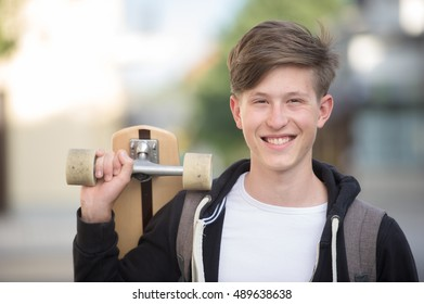 Teenager holding longboard and wearing a backpack smiling.