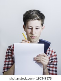 Teenager holding up notepad, pencil and calculator.
