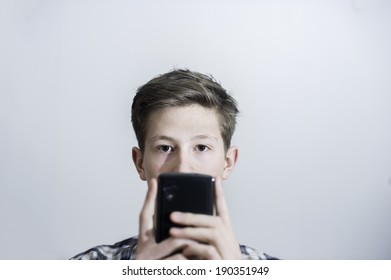 Teenager holding up phone while looking at camera.