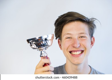 Teenager holding a trophy and smiling.
