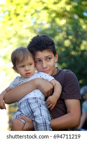 The teenager holds his younger brother in his arms. They walk in the park