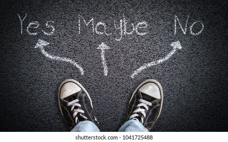 A teenager in jeans and canvas shoes standing on asphalt road with choice of Yes, Maybe, No. Concept of standing at the crossroads unable to make a decision.