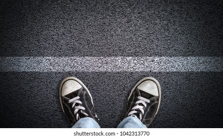 A teenager in jeans and canvas shoes standing on asphalt road behind a line with copy space. Concept of standing at a starting line, a new beginning, ready for action.