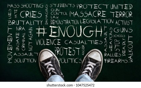 A teenager in jeans and canvas shoes standing on chalkboard with # ENOUGH word cloud. Concept of social movement to protest gun violence and mass school shootings in the United States.