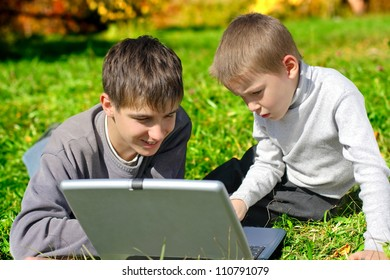 teenager and kid with notebook on the meadow