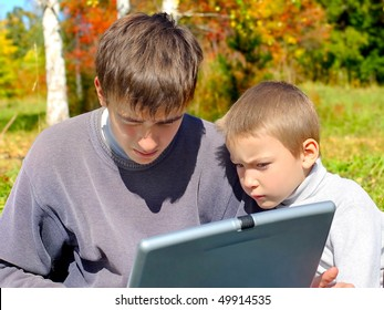 teenager and kid with notebook outdoor