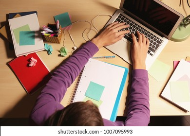 Teenager with laptop doing homework at table in evening