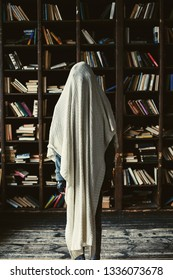 Teenager in library room with book shelfs wearing sheet looking like a ghost
