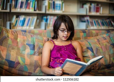 Teenager in a library is sitting on a sofa and reading a book
