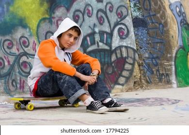 Teenager listening music near a graffiti wall