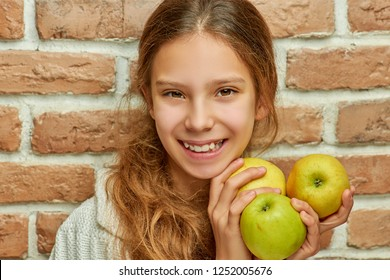 Teenager with long hair holds three apples on brick wall background.