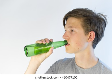 Teenager looking sad and drinking beer from a green bottle. He has a problem.