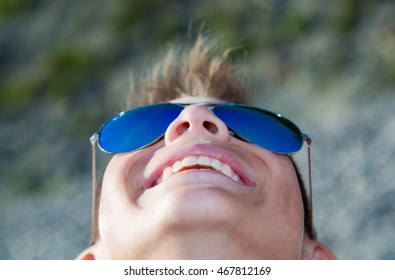 The teenager looks at the sky and smiling on the beach in blue glasses from the sun.