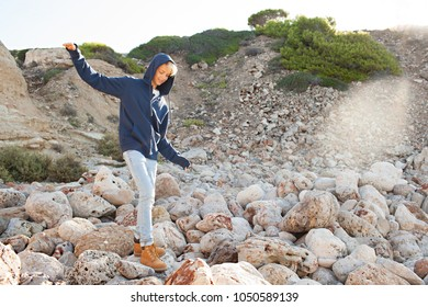 Teenager male balancing stepping walking on rocky terrain on a sunny day out, recreation in nature outdoors. Healthy young man on textured stones, active fun adventure leisure lifestyle, well being.